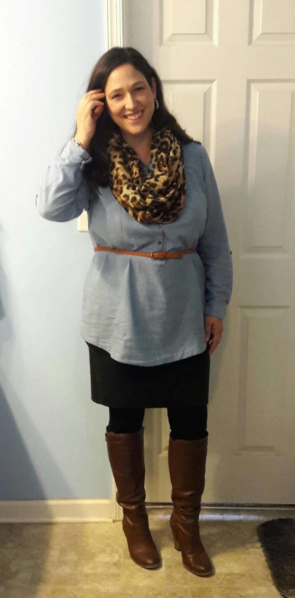 Henley Chambray Top + Brown Belt + Leopard Scarf + Black Knee-length Skirt + Leggings + Brown Riding Boots