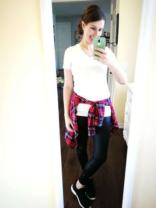 How to wear faux leather leggings in summer, spring. Casual outfit idea that covers your butt- White tee with a plaid button-down tied at waist and sneakers.